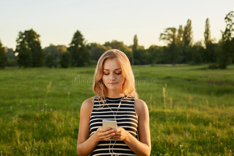 Portrait of fair-haired girl with her mobile phone and earphones royalty free stock images