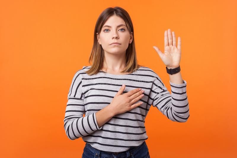 Portrait of faithful beautiful young woman with brown hair in long sleeve striped shirt. indoor studio shot isolated on orange. Portrait of faithful beautiful stock photography