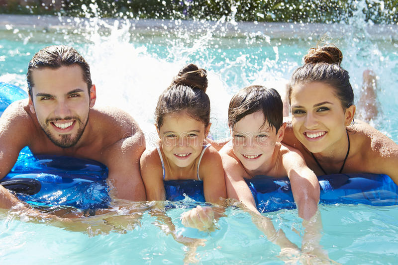 Portrait Of Family On Airbed In Swimming Pool stock photography