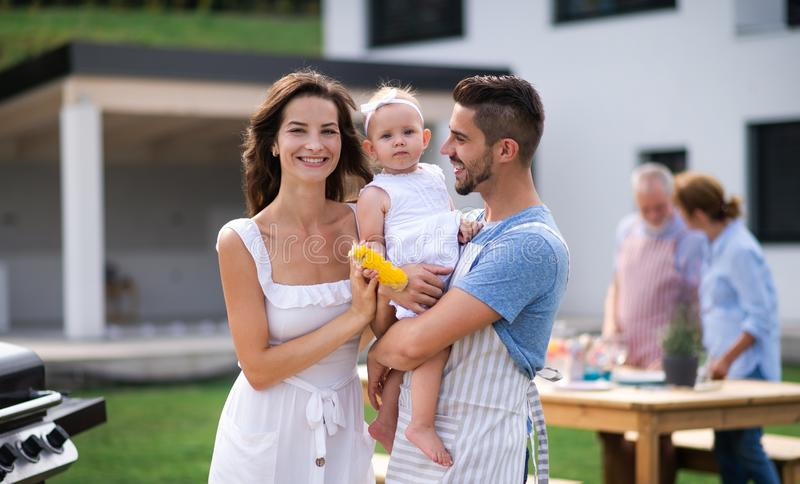 Portrait of family with baby outdoors on garden barbecue, grilling. stock photos
