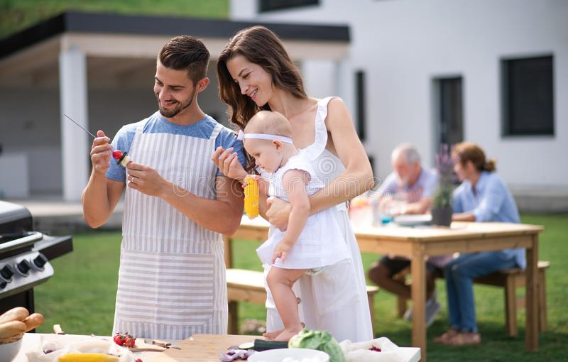 Portrait of family with baby outdoors on garden barbecue, grilling. royalty free stock images