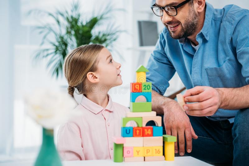 portrait of family building pyramid from colorful blocks stock photography