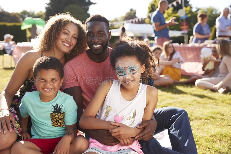 Portrait Of Family With Children Sitting On Rug At Summer Garden Fete royalty free stock photos