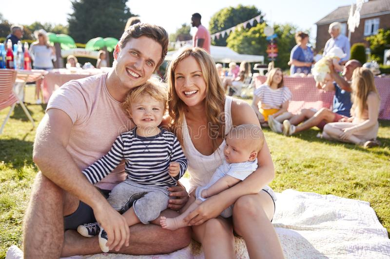 Portrait Of Family With Children Sitting On Rug At Summer Garden Fete royalty free stock photo