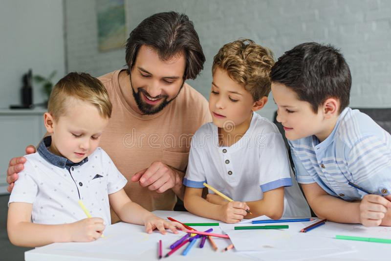 Portrait of family drawing pictures together. At home stock photo
