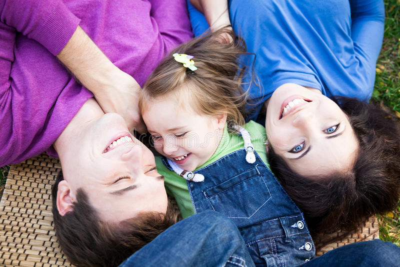 Portrait of family lying outdoors stock photo