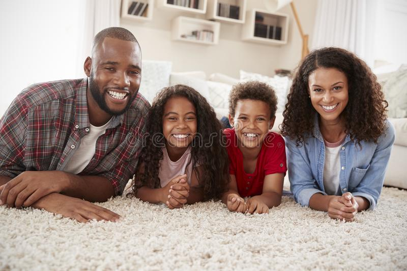 Portrait Of Family Lying On Rug In Lounge At Home stock photography