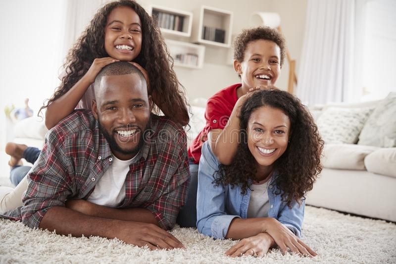 Portrait Of Family Lying On Rug In Lounge At Home royalty free stock images
