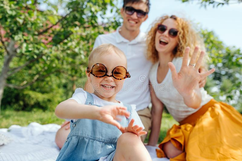 Portrait of a family, during a picnic on grass in the gardens. Summer family picnic on grass in the gardens. Mother, father and their precious infant daughter royalty free stock photography