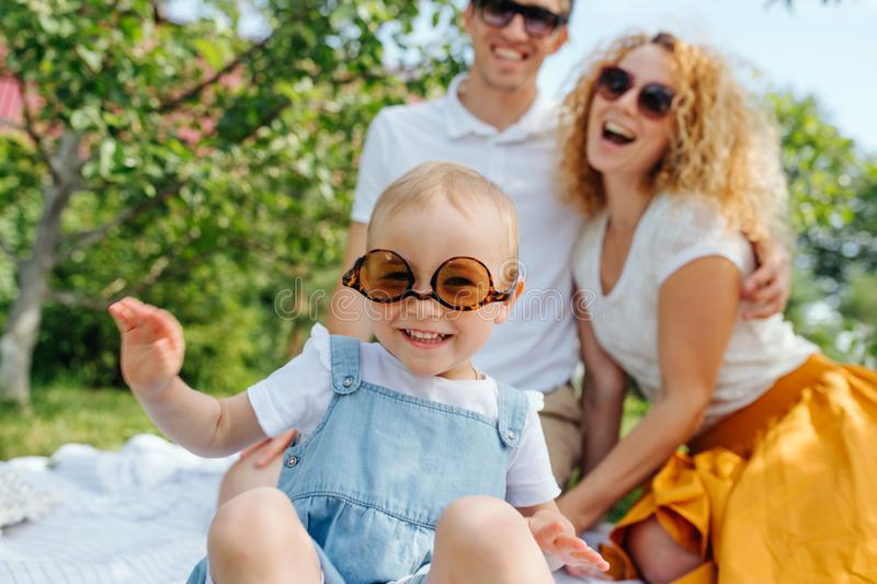 Portrait of a family, during a picnic on grass in the gardens. Summer family picnic on grass in the gardens. Mother, father and their precious infant daughter stock photo