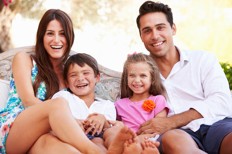Portrait Of Family Sitting On Seat In Garden At Home royalty free stock photos