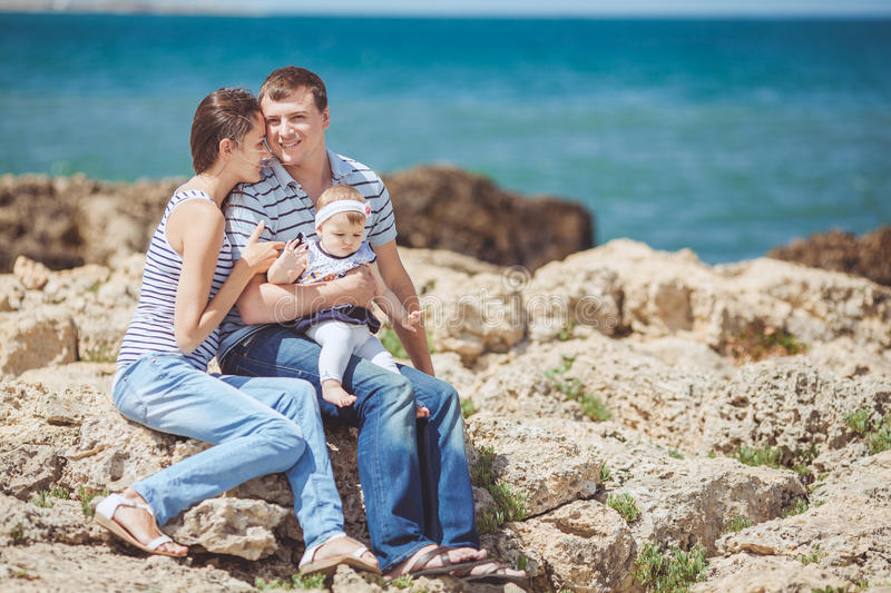 Portrait of family of three having fun together by the ocean shore and enjoying the view. Outdoors stock images