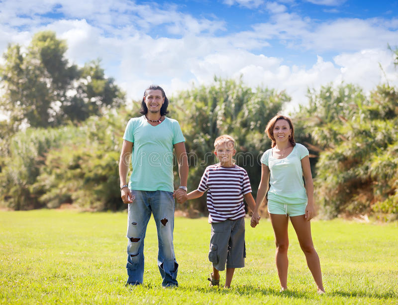 Portrait of family of three in park stock photo