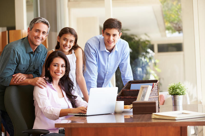 Portrait Of Family Using Laptop Together. Portrait Of Hispanic Family Using Laptop Together At Home Smiling To Camera stock photo
