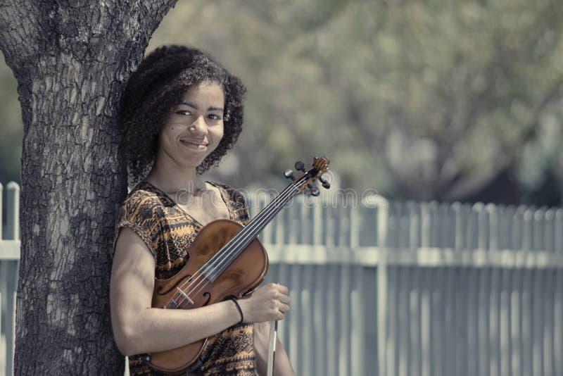 Portrait fané de jeune femme tenant le violon dehors photo stock