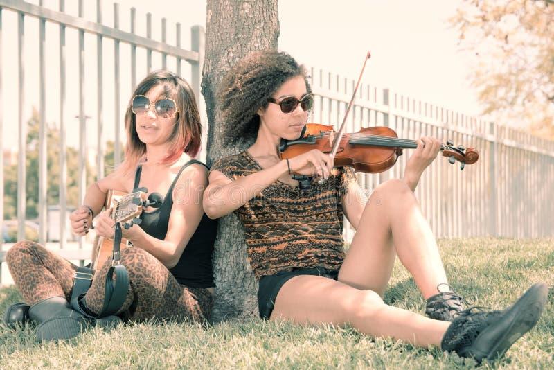 Portrait fané des musiciens féminins assis sous l'arbre photographie stock libre de droits