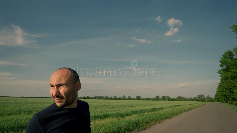 Portrait of a farmer on the background of a field and a road. royalty free stock images
