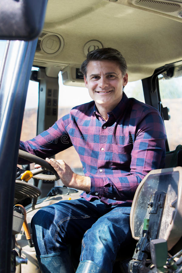 Portrait Of Farmer Sitting In Cab Of Tractor royalty free stock photography