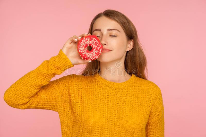 Portrait of fascinating hungry ginger girl in sweater smelling doughnut and expressing desire to eat sweet donut royalty free stock photo