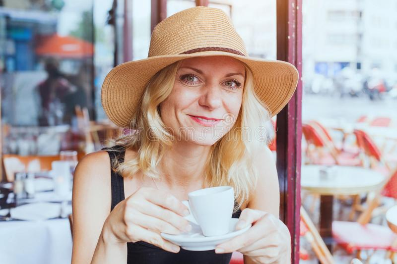 Portrait of fashion beautiful middle aged woman in cafe with cup of coffee, happy smile royalty free stock images
