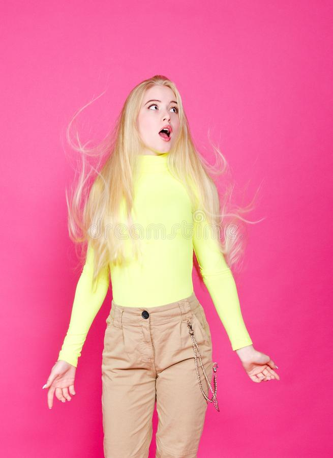 Portrait of fashion blonde surprised model girl young woman wearing stylish  on a pink stock photo