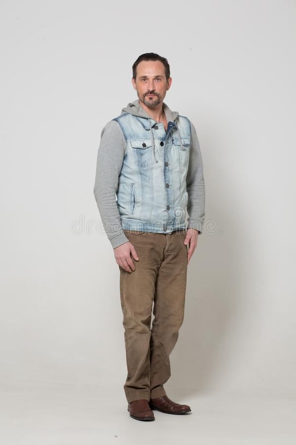 Portrait of fashion dressed man. Real strong men with open look. Standing on white background royalty free stock image