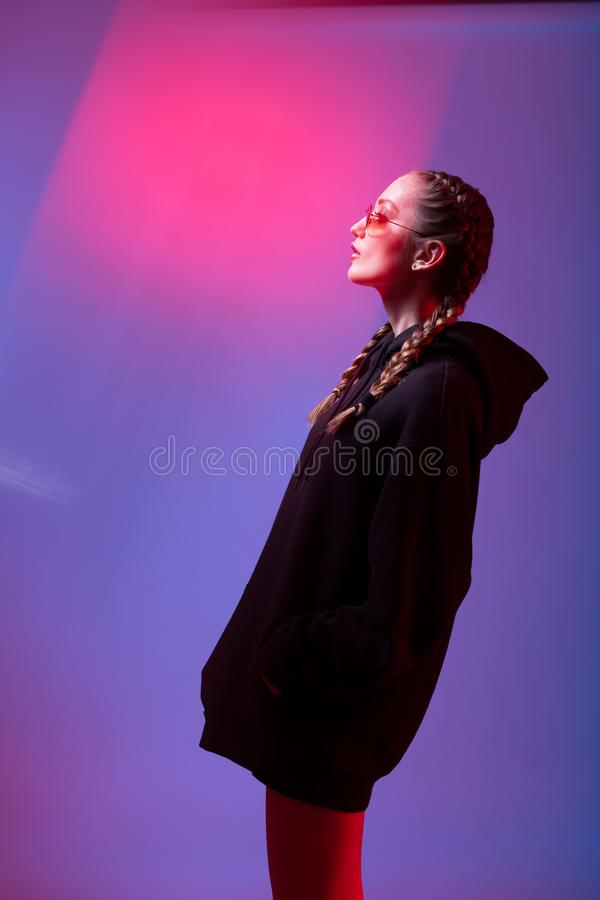 Portrait of fashion girl in a black sweater with a hood and sunglasses round shape in neon light in the studio royalty free stock photography