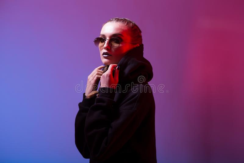 Portrait of fashion girl in a black sweater with a hood and sunglasses round shape in neon light in the studio stock images