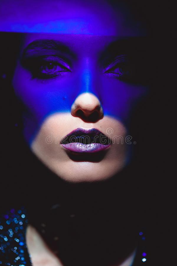 Portrait of fashion girl with stylish makeup and blue neon light on her face on the black background in the studio stock photos