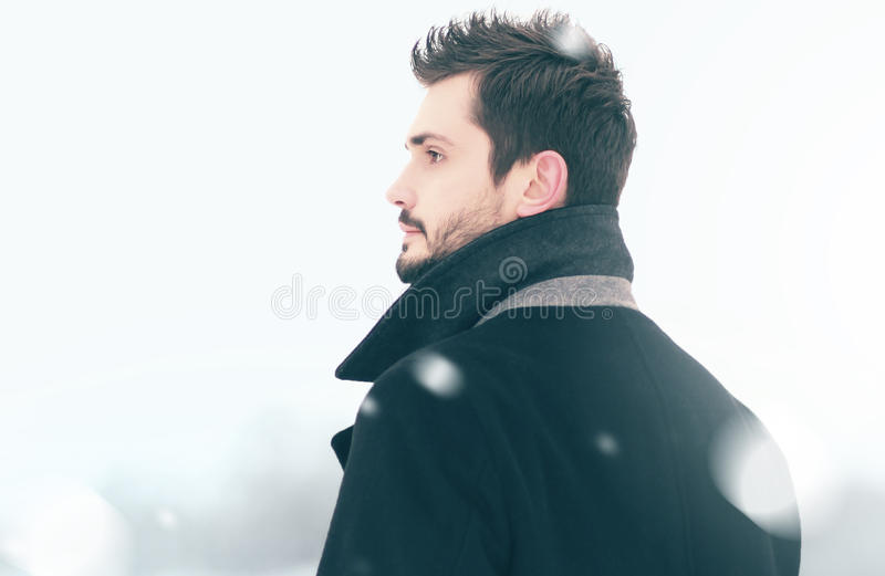 Portrait of fashion handsome man in winter snowstorm looks, profile view royalty free stock images