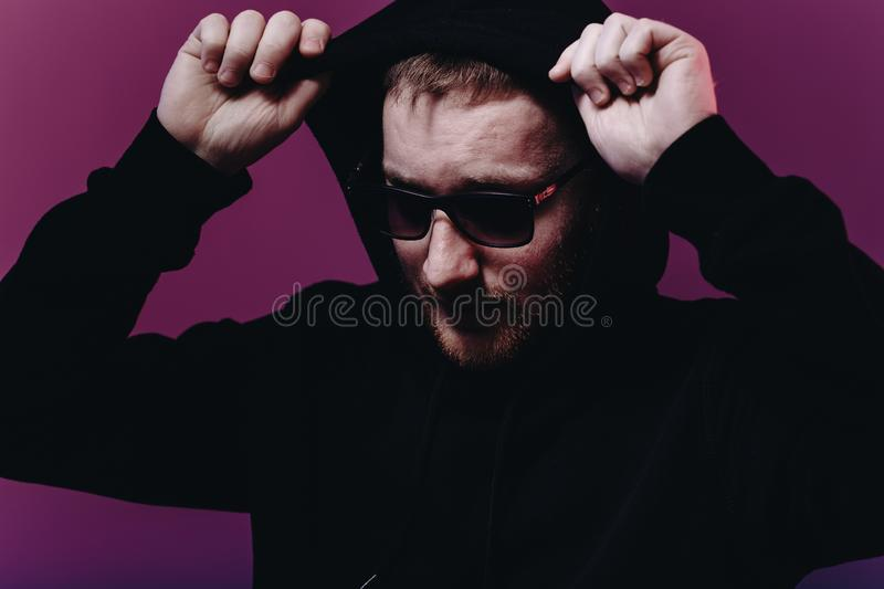 Portrait of fashion man in a black sweater with a hood and sunglasses in neon light in the studio royalty free stock photography