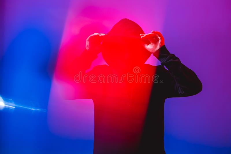 Portrait of fashion man in a black sweater with a hood and sunglasses in neon light in the studio stock photography