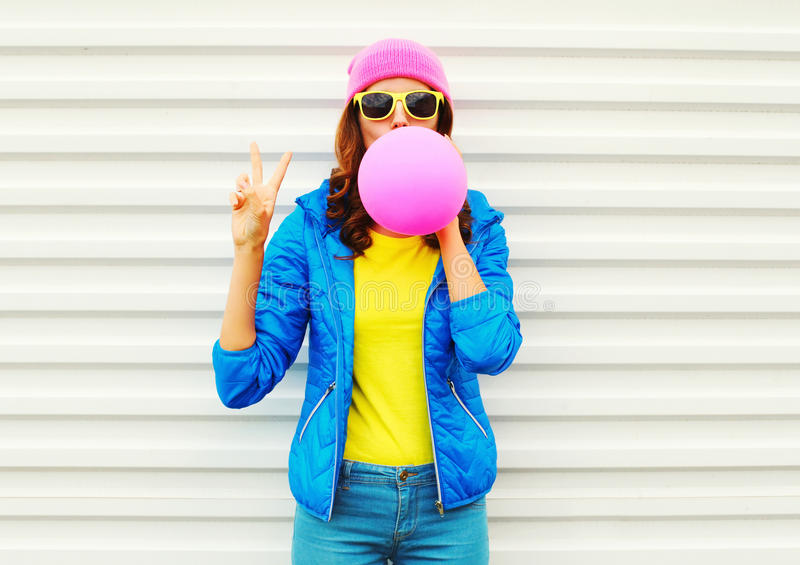 Portrait fashion pretty cool girl blowing pink air balloon in colorful clothes having fun over white background wearing a pink hat stock images