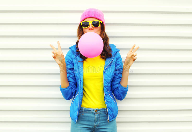 Portrait of fashion pretty cool girl blowing pink air balloon in colorful clothes having fun over white wearing a pink hat stock photography