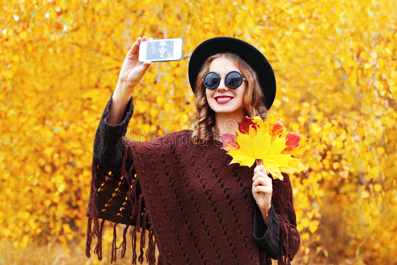 Portrait fashion smiling young woman taking autumn picture makes self portrait on smartphone over sunny yellow leaves royalty free stock photos