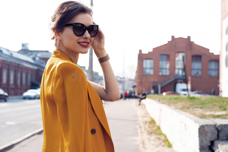 Portrait fashion woman in sunglasses walking on street . She wears yellow jacket, smiling to side. stock photos