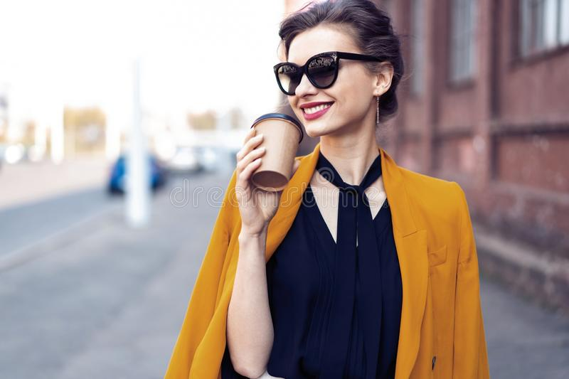 Portrait fashion woman in sunglasses walking on street . She wears yellow jacket, smiling to side. stock photo