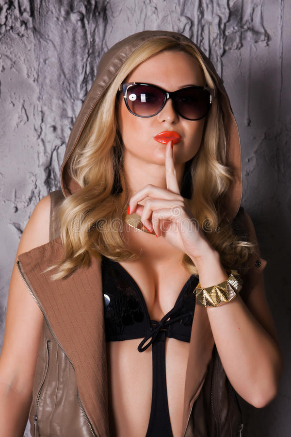 Portrait of a fashion woman. Portrait of a young woman in sunglasses over grey background stock images