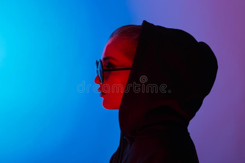 Portrait of fashion young girl in a black sweater with a hood and round sunglasses in red and blue neon light in the stock image