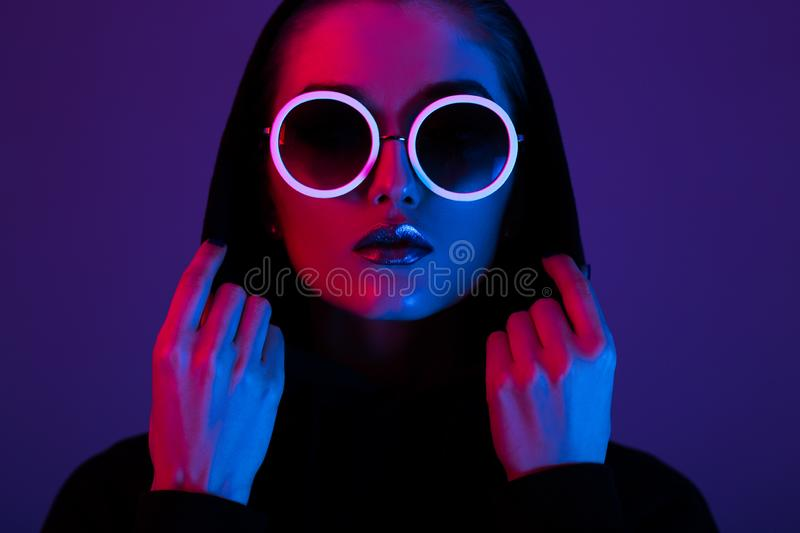 Portrait of fashion young girl in a black sweater with a hood and round sunglasses in red and blue neon light in the royalty free stock image