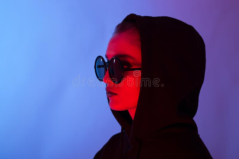 Portrait of fashion young girl in a black sweater with a hood and round sunglasses in red and blue neon light in the stock photography