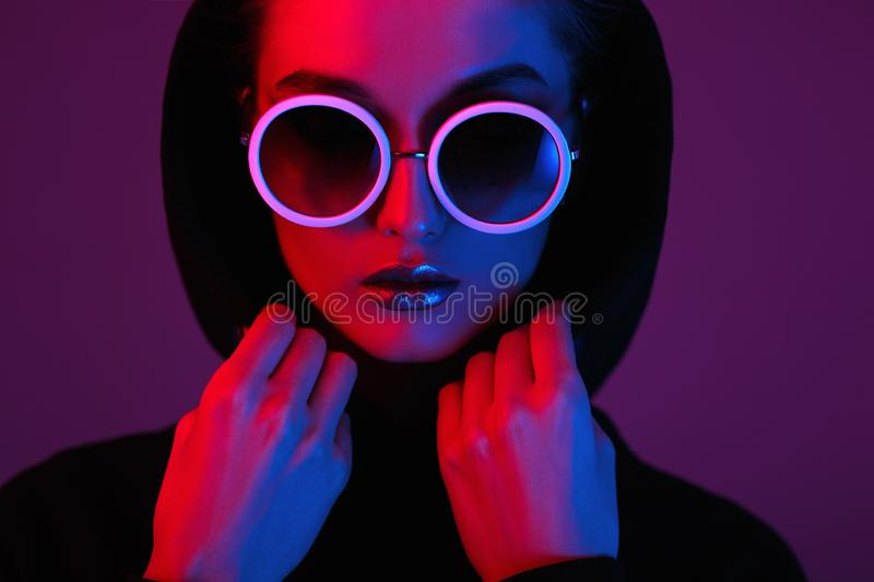 Portrait of fashion young girl in a black sweater with a hood and round sunglasses in red and blue neon light in the royalty free stock photo