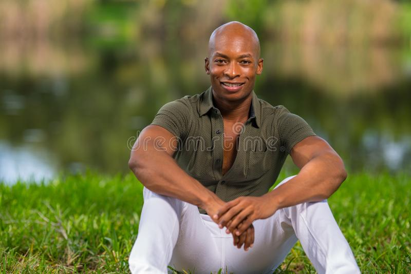 Portrait fashionable African American man sitting on grass in the park. Man is smiling and looking at camera stock photography