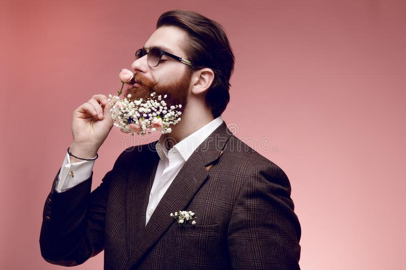 Portrait of a attractive brutal bearded man in sunglasses with flowers in beard, isolated on a dark pink background. stock photo