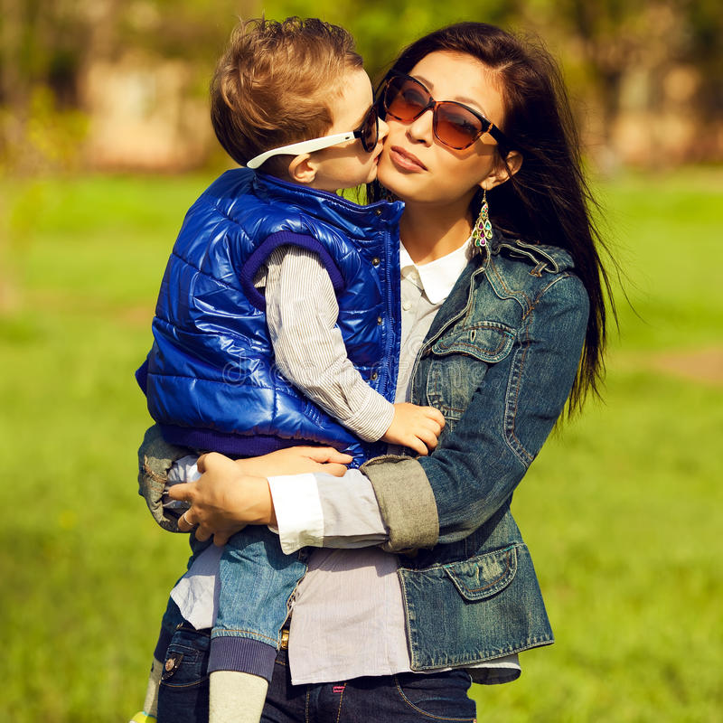 Portrait of fashionable baby boy and his gorgeous mother. (hollywood star) in trendy sunglasses walking in the street. Kid kissing mom. Sunny spring day stock images