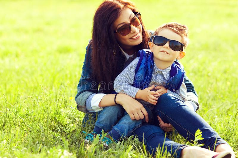 Portrait of fashionable baby boy and his stylish mother. In trendy sunglasses sitting on green grass in the park. Sunny spring day. Hipster style. Copy-space stock photos