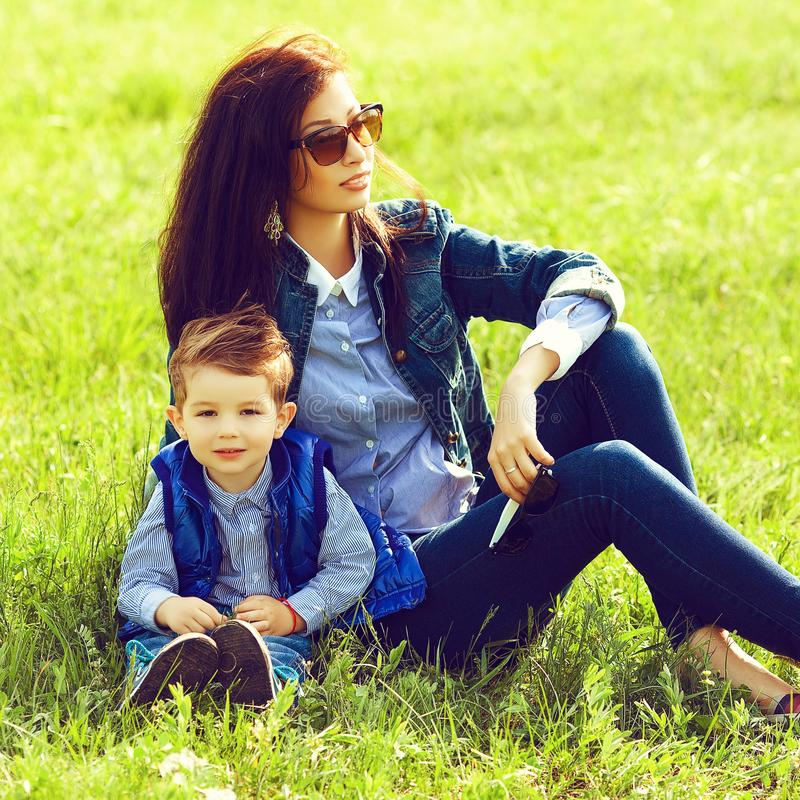 Portrait of fashionable baby boy and his stylish mother in trend. Y sunglasses sitting on green grass in the park. Sunny spring day. Hipster style. Outdoor shot stock images