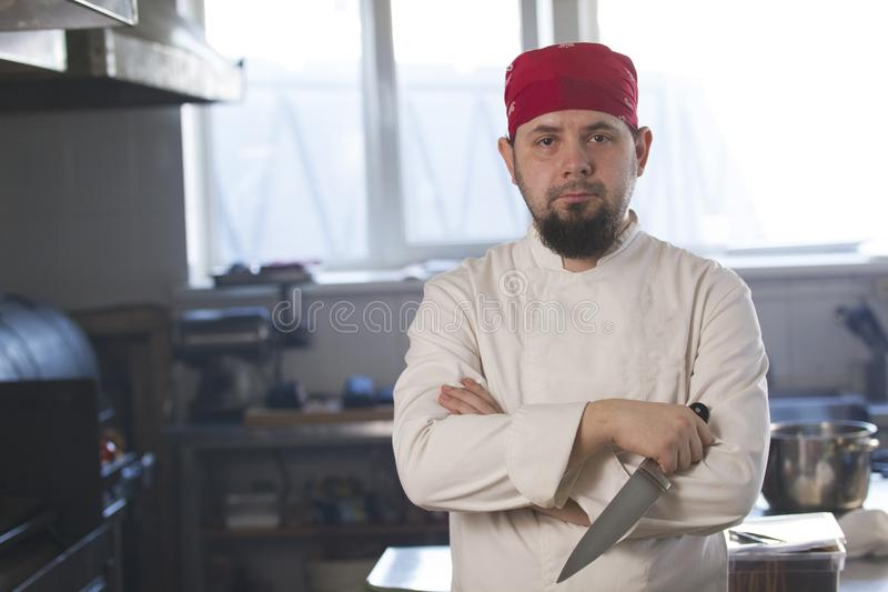 Portrait of a fashionable chef in bandana holding a knife in a kitchen stock image