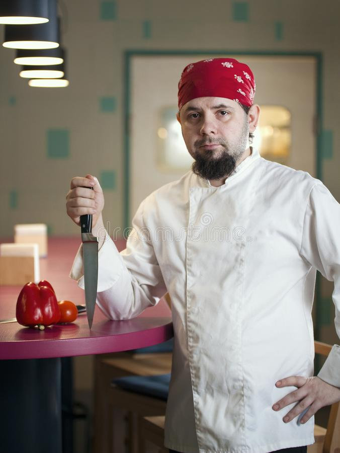 Portrait of a fashionable chef with a knife in bandana royalty free stock photos