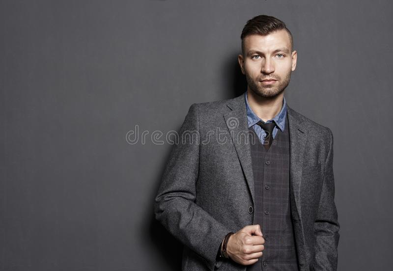 Portrait of fashionable confident handsome man in suit on gray wall background. Businessman looks seriously look royalty free stock photography